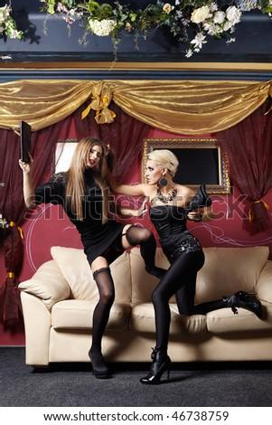 Two stylish girls fight in night club - stock photo