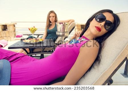 two stylish girls sitting in beach chairs enjoying the tropical weather / summer holidays and vacations - stock photo