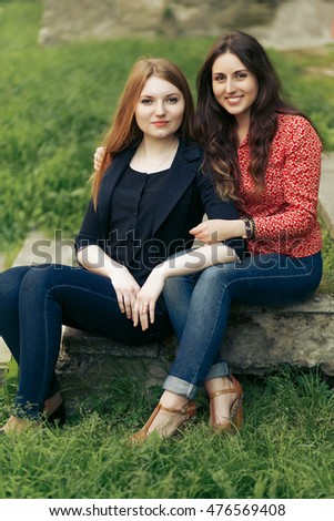 two stylish happy woman hugging in europe city park, sincere moments friendship concept