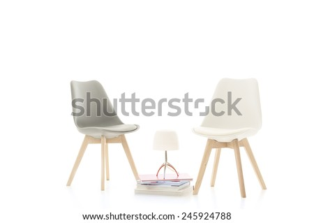 Two stylish modern chairs facing each other with an elegant lamp on a stack of hardcover books between them conceptual of dialogue and discussion, over a white background - stock photo