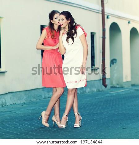 Two stylish trendy beautiful girl talking on the street - stock photo