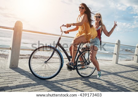 Two stylish young female friends on a bicycle along seaside. Best friends enjoying a day on bike.