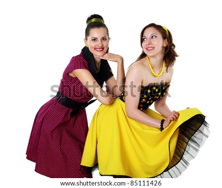 two stylish young woman in bright colour dresses - stock photo