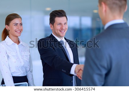 Two successful business men shaking hands with each other . - stock photo
