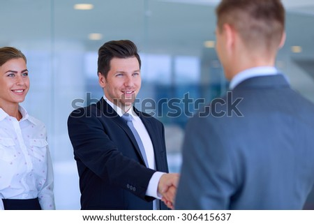 Two successful business men shaking hands with each other .