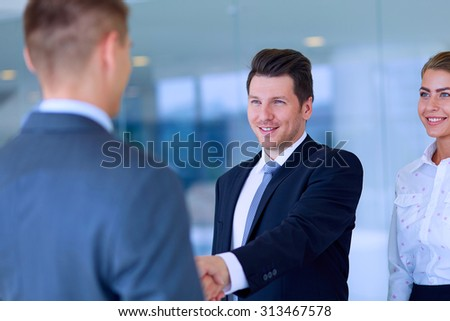 Two successful business men shaking hands with each other - stock photo