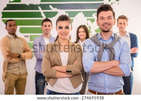Two successful business people are standing on background of colleagues. - stock photo