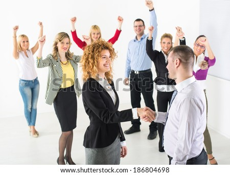 Two successful business people shaking hands at the meeting. Group their colleague celebrating in the background. - stock photo