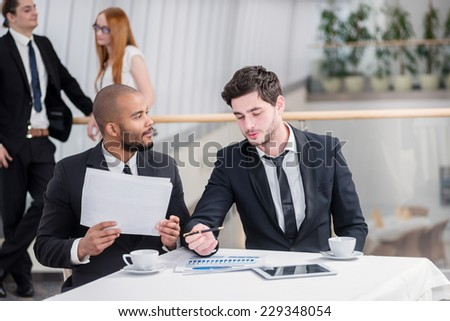 Two successful businessman sitting at a desk holding papers in his hands and looking into the camera while their colleagues standing in the background and shake hands - stock photo