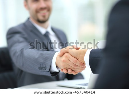 Two successful businessman sitting at the table and shaking hands - stock photo