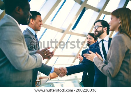 Two successful businessmen handshaking while their colleagues clapping their hands - stock photo