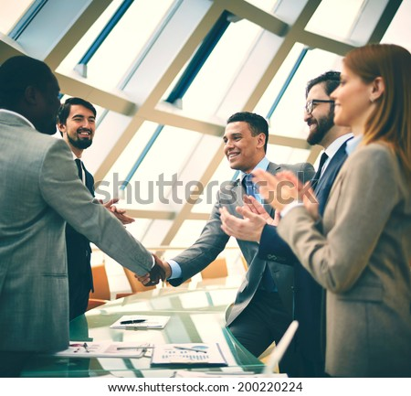 Two successful businessmen handshaking while their colleagues congratulating them - stock photo