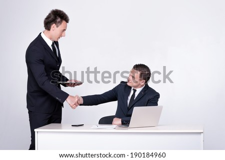 Two successful businessmen shake hands at table and talking in office.