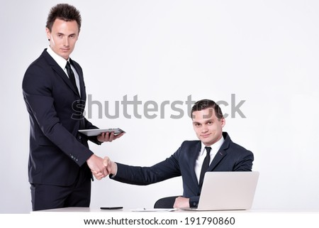 Two successful businessmen shake hands at table and talking in office. Handsome men are sitting at laptop working on the tablet. Confident businessmen smiling  in formal wear and writing on paper