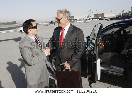 Two successful businessmen shaking hands while standing by car at airfield - stock photo