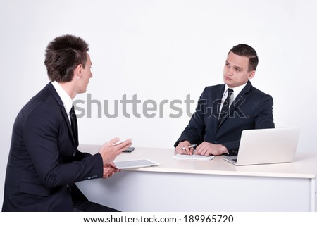 Two successful businessmen sitting at desk and have conversation in office.Handsome men are sitting at laptop working on the tablet. Confident businessmen smiling  in formal wear and writing on paper - stock photo