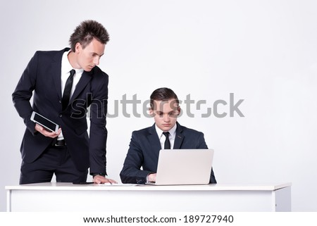 Two successful businessmen sitting at table and talking in office. Handsome men are sitting at laptop working on the tablet. Confident businessmen smiling in formal wear and writing on paper