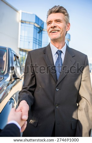 Two  successful businesspeople in suits   shaking hands standing near car. - stock photo