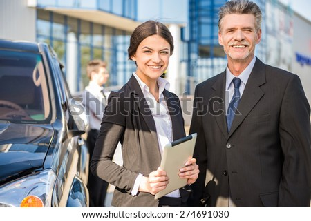 Two  successful confident businesspeople in suits   at a meeting  standing near car. - stock photo