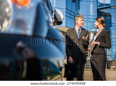 Two  successful confident businesspeople in suits  talking at a meeting near car. - stock photo