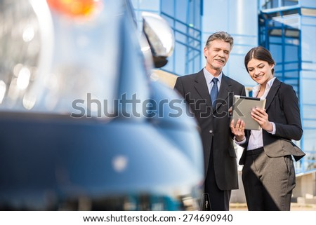 Two  successful confident businesspeople in suits   using tablet near car. - stock photo