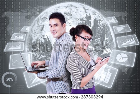 Two successful entrepreneurs using laptop and tablet in front of futuristic interface with global financial statistics