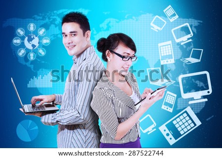 Two successful entrepreneurs working with laptop computer and tablet, shot with futuristic interface