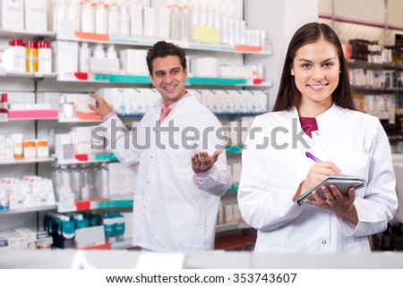Two successful friendly pharmacists working in modern farmacy