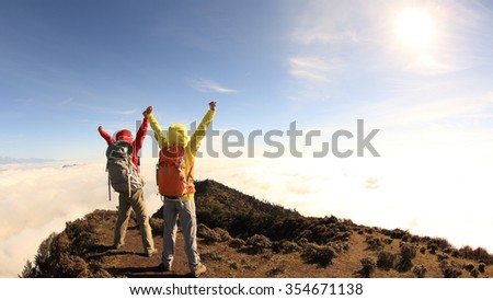 two successful hikers cheering to sunrise on mountain peak - stock photo