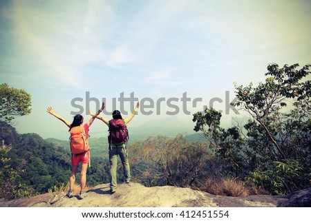 two successful hiking friends enjoy the view on mountain peak - stock photo