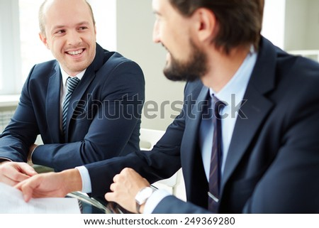 Two successful male colleagues interacting at meeting