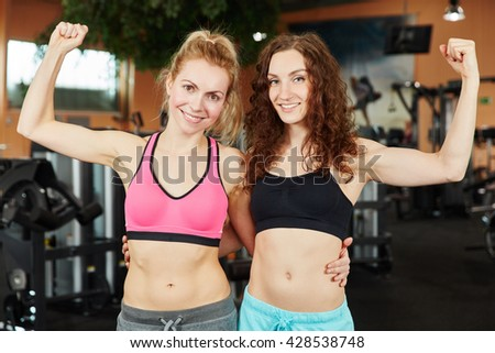 Two successful women as a team cletching their fists at the gym - stock photo