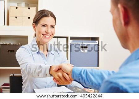 Two sucessful business partner shaking hands in the office - stock photo