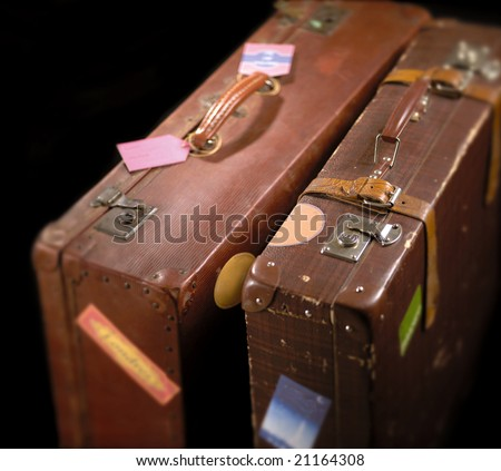 Two suitcases over black background, with shallow focus - stock photo