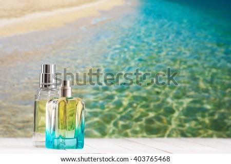 Two summer perfumes on white wooden table against defocused coastline.