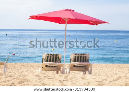 Two sun beds with umbrella on a tropical beach with a beautiful ocean view - stock photo