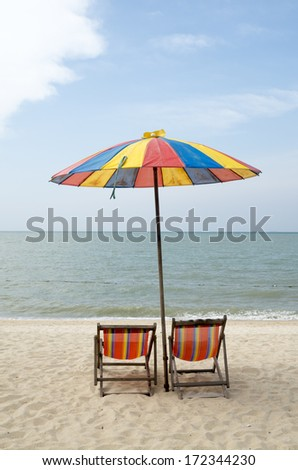 Two sun loungers and an umbrella on a sunny day