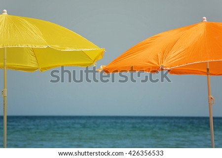 two sun shield umbrellas against sea scape background