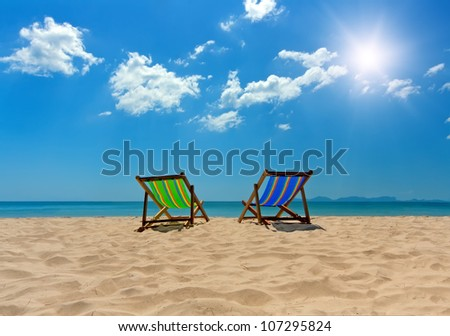 Two sunbeds on a beautiful tropical beach - stock photo