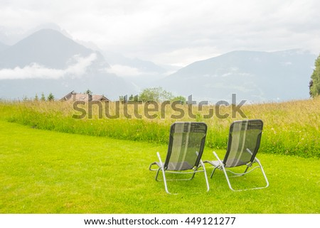 Two sunbeds on grass with mountain background