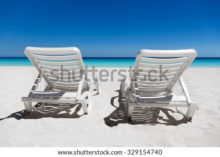 Two sunbeds on tropical calm beach with turquoise caribbean sea water and white sand  - stock photo