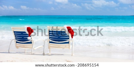 Two sunloungers with Santa hats on beautiful tropical beach with white sand and turquoise water, perfect Christmas vacation - stock photo