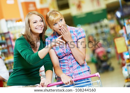 Two suprised amazed women with shopping cart at supermarket shopping mall store - stock photo
