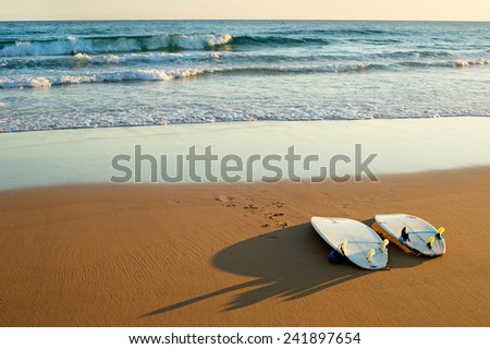 Two surfboards lying on the beach at sunset - stock photo