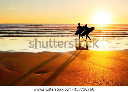 Two surfer running on the beach at sunset. Portugal