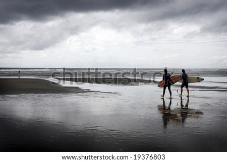 Two surfers head towards the ocean under storm clouds - stock photo