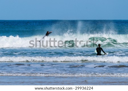 Two surfers in Newquay, Cornwall, England. - stock photo