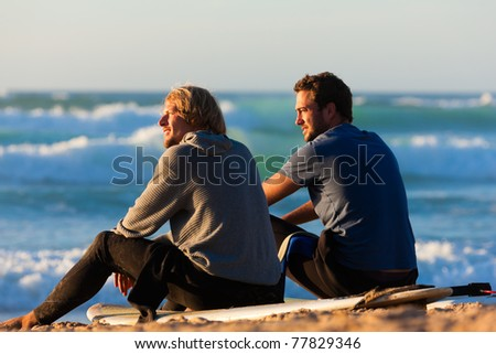 Two surfers sitting on their surf boards on the beach discussing the waves