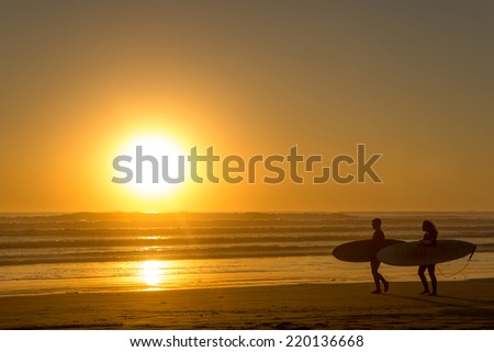 two surfers walking on the beach with their surfboard in the light of the setting sun over the ocean - stock photo