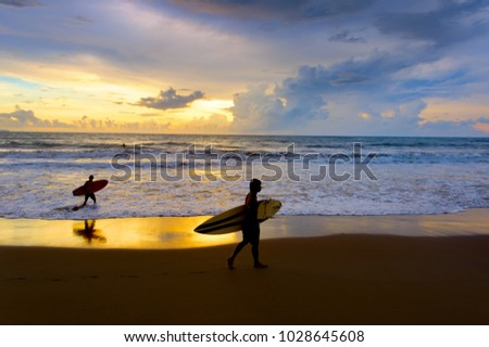 Two surfers with surfboard walking on the ocean beach at sunset. Bali island, Indonesia